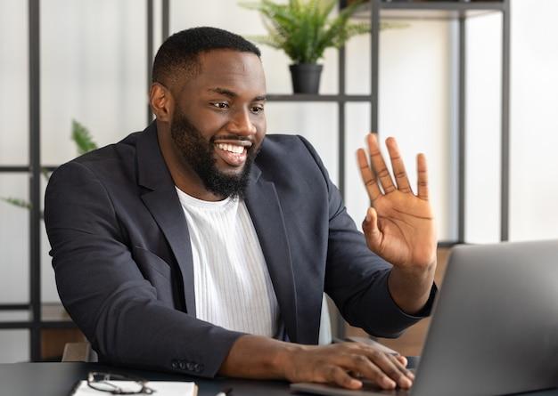Lächelnder junger afroamerikanischer mann, der am schreibtisch sitzt, winkt, spricht über videoanrufe online. zoom konferenzkonzept