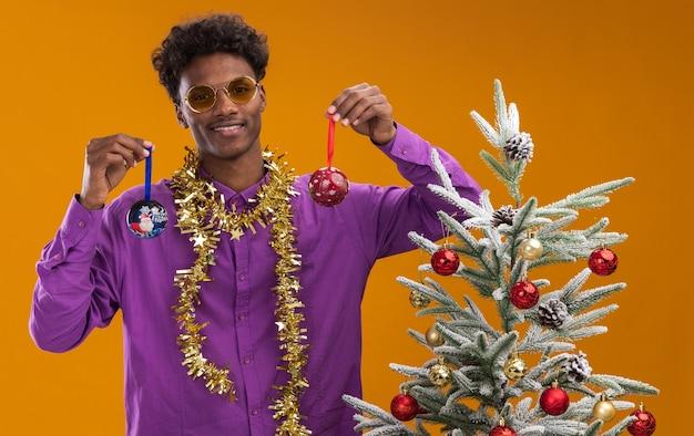 Lächelnder junger afroamerikanischer mann, der brille mit lametta-girlande um den hals trägt, der nahe verziertem weihnachtsbaum auf orange hintergrund steht