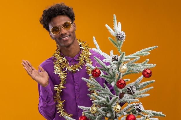 Lächelnder junger afroamerikanischer mann, der eine brille mit lametta-girlande um den hals trägt, der hinter geschmücktem weihnachtsbaum steht, der leere hand lokalisiert auf orange wand zeigt