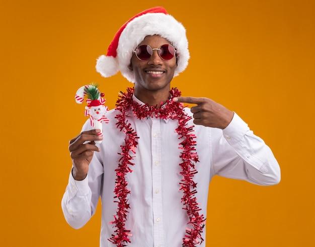 Lächelnder junger afroamerikanischer mann, der weihnachtsmütze und brille mit lametta-girlande um den hals hält und auf zuckerstangenverzierung zeigt, die kamera lokalisiert auf orange hintergrund trägt