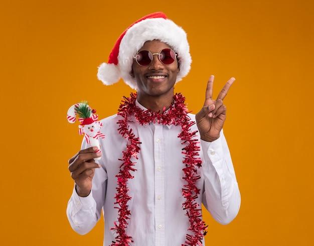 Lächelnder junger afroamerikanischer mann, der weihnachtsmütze und brille mit lametta-girlande um hals hält, der zuckerstangenverzierung tut, die friedenszeichen lokalisiert auf orange wand hält
