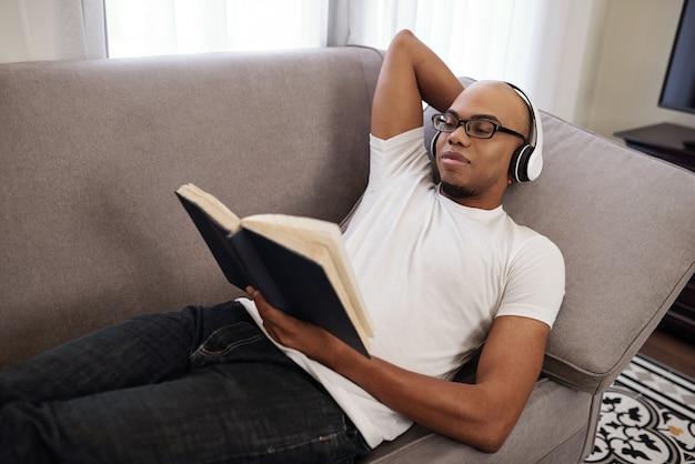Lächelnder junger afroamerikanischer mann im kopfhörer, der sich auf sofa entspannt und interessanten roman liest