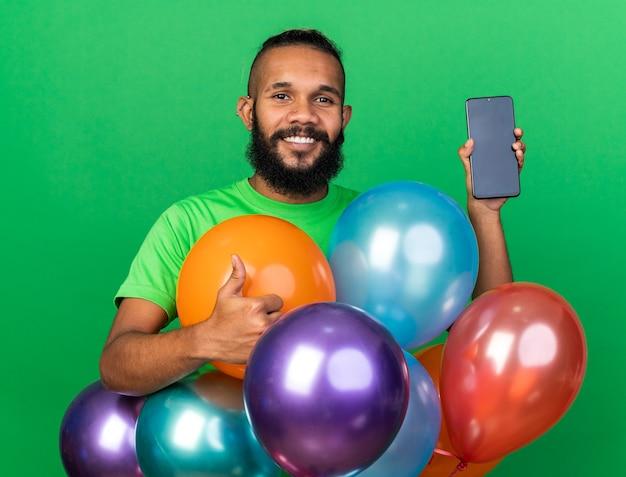 Lächelnder junger afroamerikanischer mann mit grünem t-shirt, der hinter ballons mit telefon steht