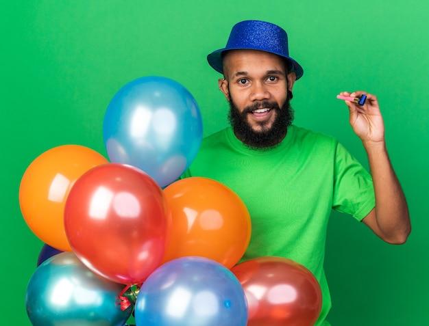 Lächelnder junger afroamerikanischer mann mit partyhut, der luftballons mit partypfeife isoliert auf grüner wand hält