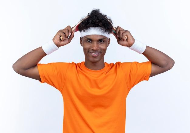Lächelnder junger afroamerikanischer sportlicher mann, der stirnband und armband bedeckte kopf mit tischtennisschläger lokalisiert auf weißer wand trägt