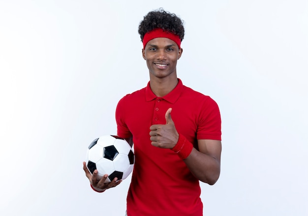 Lächelnder junger afroamerikanischer sportlicher mann, der stirnband und armband hält, hält ball seinen daumen oben isoliert auf weiß