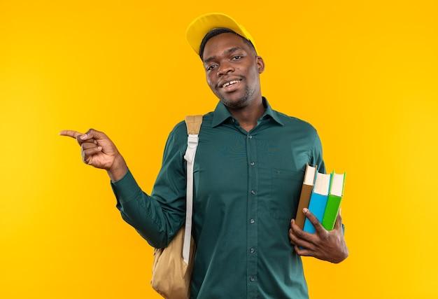 Lächelnder junger afroamerikanischer student mit mütze und rucksack, der bücher hält und auf die seite zeigt, isoliert auf oranger wand mit kopierraum
