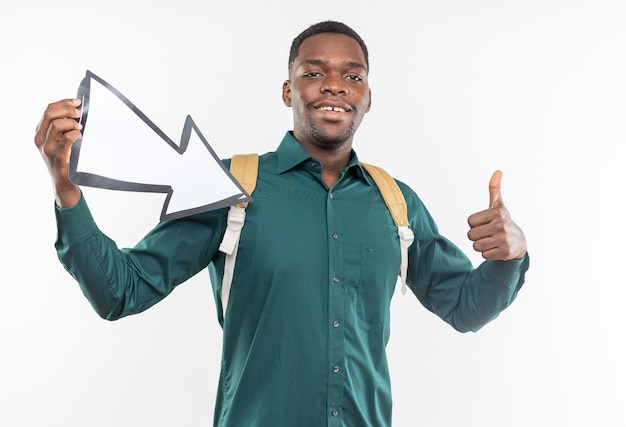 Lächelnder junger afroamerikanischer student mit rucksack, der einen pfeil hält, der auf die seite zeigt und nach oben zeigt