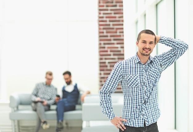 Lächelnder junger angestellter, der im büro steht