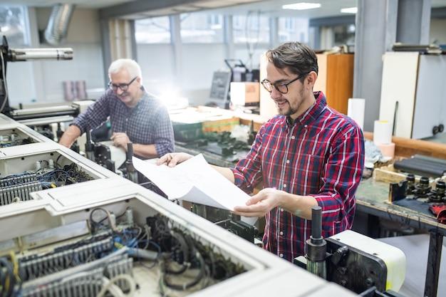 Lächelnder junger arbeiter im freizeithemd, der an druckmaschine steht und bedrucktes papier prüft