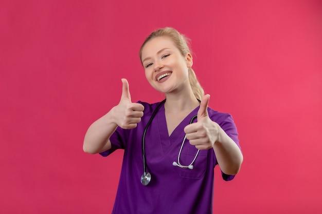 Lächelnder junger arzt, der lila medizinisches kleid trägt und ihre daumen auf isolierte rosa wand stethoskopiert