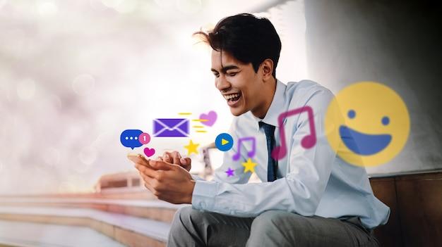 Lächelnder junger asiatischer geschäftsmann mit handy in der stadt. genießen sie social media-anwendung. umgeben von vielen ikonen