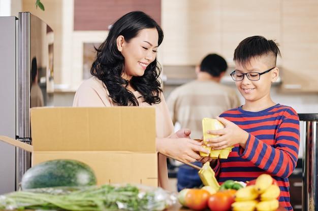 Lächelnder junger asiatischer junge, der mutter hilft, frische lebensmittel aus pappkarton zu nehmen