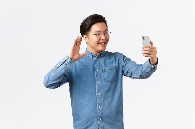 Lächelnder junger asiatischer kerl, college-student in brille und zahnspange, der familie anruft, videoanruf-app verwendet, auf die smartphone-kamera winkt, um hallo zu sagen, freund begrüßt, der mit anhängern in sozialen medien chattet.