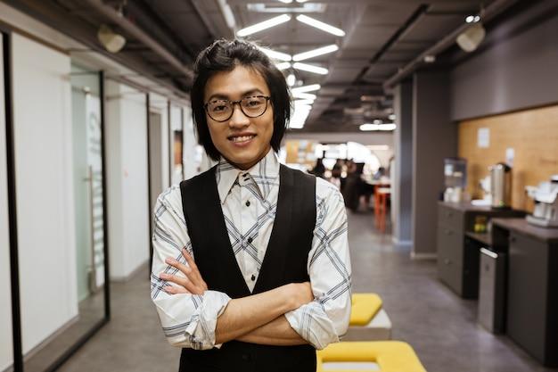 Lächelnder junger asiatischer mann, der brille in der jacke trägt