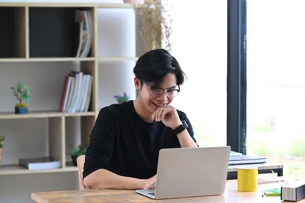 Lächelnder junger asiatischer mannunternehmer, der mit laptop-computer arbeitet.