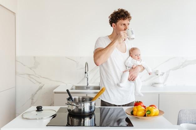 Lächelnder junger attraktiver vater, der nudeln kocht, während er seinen kleinen sohn in der küche zu hause hält