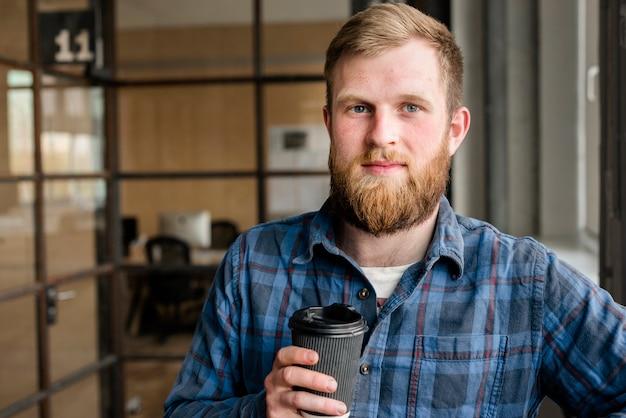 Lächelnder junger bärtiger mann, der die wegwerfkaffeetasse betrachtet kamera hält