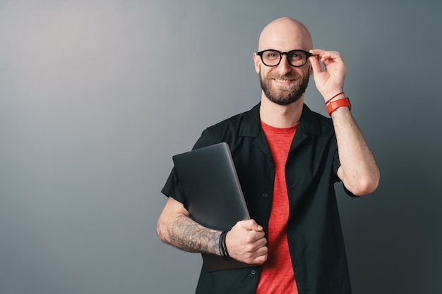 Lächelnder junger bärtiger mann, der laptop unter dem arm hält und seine brille mit den fingern berührt, im studio auf grau