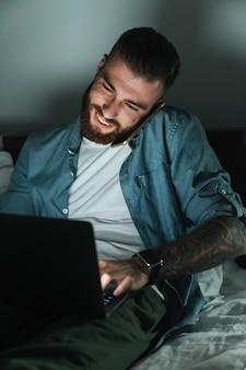 Lächelnder junger bärtiger mann, der nachts zu hause auf dem bett liegt und mit dem handy spricht, während er am laptop arbeitet?