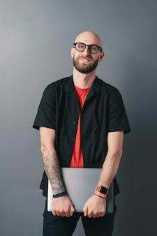 Lächelnder junger bärtiger mann mit brille, die laptop unter seinen armen im studio auf grau hält