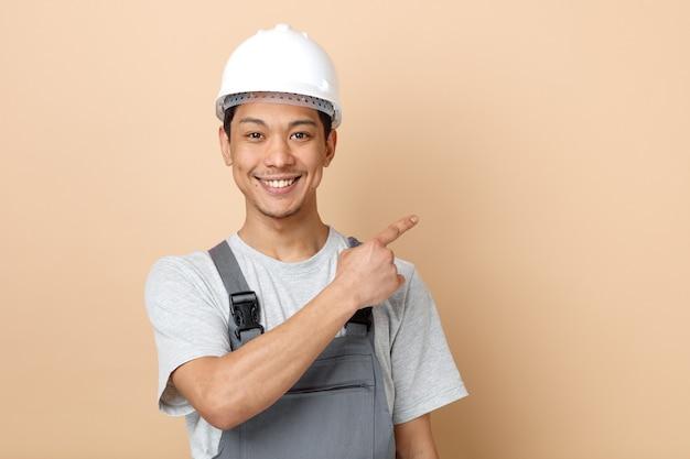 Lächelnder junger bauarbeiter, der schutzhelm und uniform trägt, zeigt an ecke