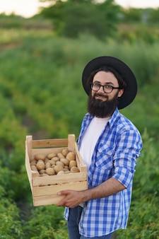 Lächelnder junger bauer mit holzkiste kartoffeln auf grünem kartoffelfeld