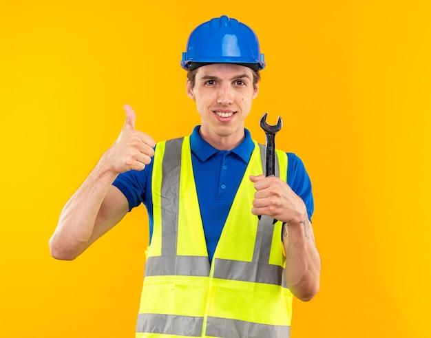 Lächelnder junger baumeister in uniform, der einen gabelschlüssel hält, der daumen nach oben isoliert auf gelber wand zeigt