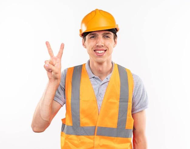 Lächelnder junger baumeister in uniform mit friedensgeste isoliert auf weißer wand