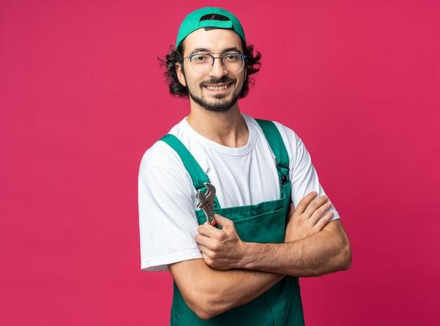 Lächelnder junger baumeister in uniform mit mütze, die einen offenen schraubenschlüssel hält, der die hände kreuzt