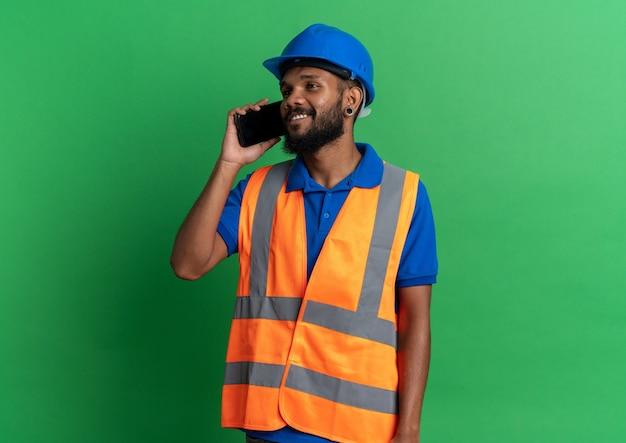 Lächelnder junger baumeister in uniform mit schutzhelm, der am telefon spricht und die seite isoliert auf grüner wand mit kopierraum betrachtet
