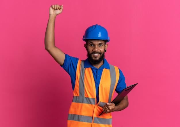 Lächelnder junger baumeister in uniform mit schutzhelm, der mit erhobener faust steht und die zwischenablage isoliert auf rosa wand mit kopierraum hält