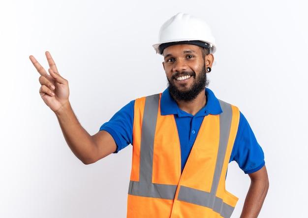 Lächelnder junger baumeister in uniform mit schutzhelm gestikuliert siegeszeichen isoliert auf weißer wand mit kopierraum