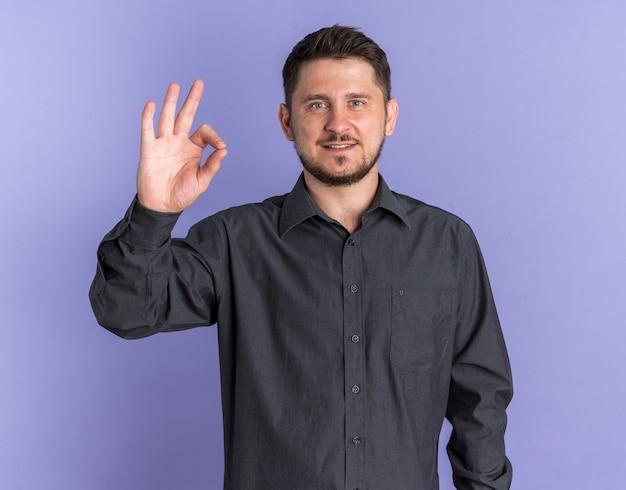 Lächelnder junger blonder gutaussehender mann zeigt zeichen, dass es in ordnung ist, wenn man die vorderseite isoliert auf der marinewand betrachtet