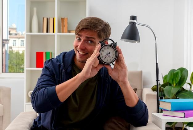 Lächelnder junger blonder hübscher mann sitzt auf sessel, der wecker im wohnzimmer hält