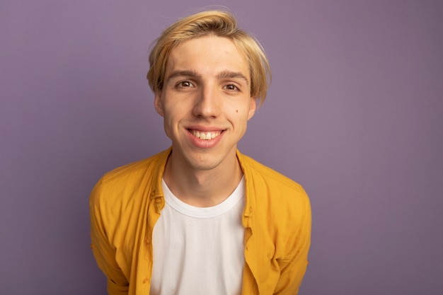 Lächelnder junger blonder kerl, der gelbes t-shirt trägt
