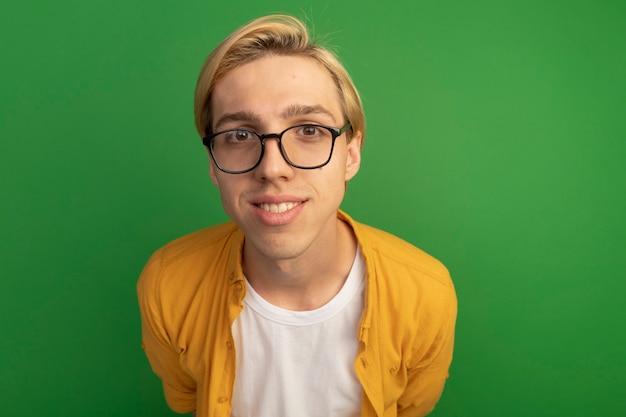 Lächelnder junger blonder kerl, der gelbes t-shirt und brille trägt