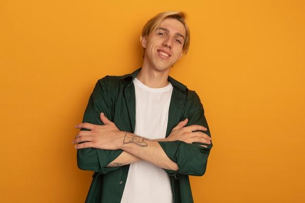 Lächelnder junger blonder kerl, der grünes t-shirt trägt, das hände kreuzt