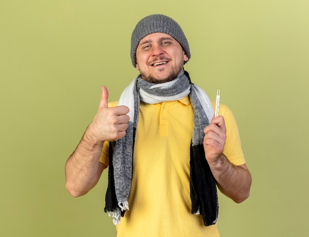 Lächelnder junger blonder kranker slawischer mann, der wintermütze und schal daumen hoch trägt