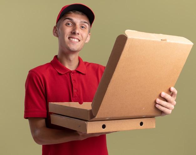 Lächelnder junger blonder lieferbote hält pizzakartons