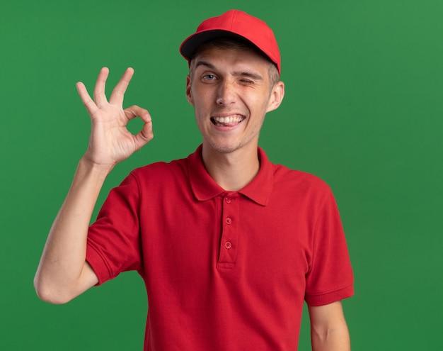 Lächelnder junger blonder lieferjunge blinzelt mit den augen und gestikuliert ok handzeichen isoliert auf grüner wand mit kopierraum