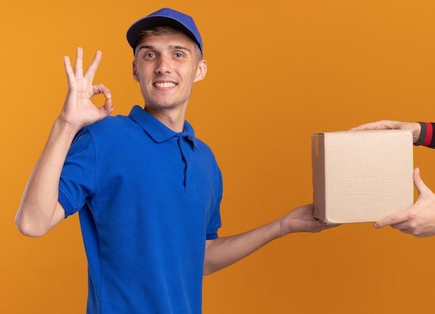 Lächelnder junger blonder lieferjunge, der jemandem karton gibt und ok handzeichen gestikuliert