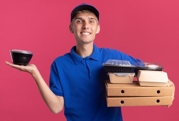 Lächelnder junger blonder lieferjunge, der lebensmittelbehälter und -verpackungen auf pizzaschachteln auf rosa hält