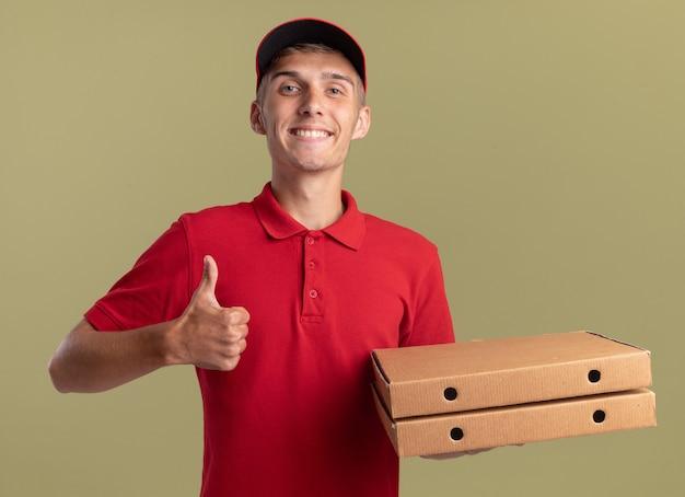 Lächelnder junger blonder lieferjunge, der nach oben blättert und pizzaschachteln auf olivgrün hält