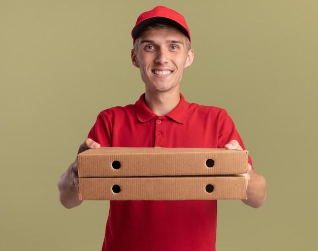 Lächelnder junger blonder lieferjunge, der pizzaschachteln auf olivgrün hält