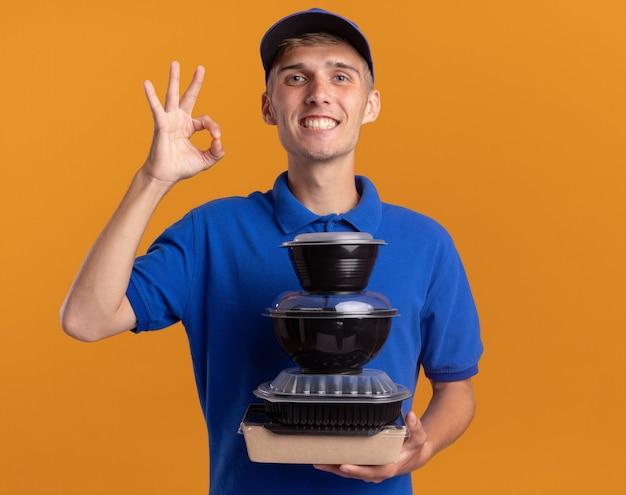 Lächelnder junger blonder lieferjunge gestikuliert ok handzeichen und hält lebensmittelbehälter isoliert auf oranger wand mit kopierraum
