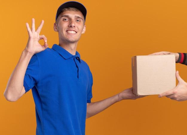 Lächelnder junger blonder lieferjunge gibt jemandem karton und gesten ok handzeichen isoliert auf oranger wand mit kopierraum