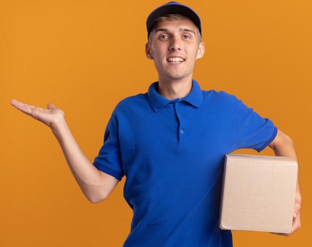 Lächelnder junger blonder lieferjunge hält hand offen und hält kartenbox isoliert auf orange wand mit kopienraum