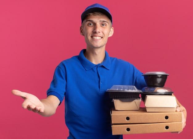 Lächelnder junger blonder lieferjunge hält hand offen und hält lebensmittelbehälter und -verpackungen auf pizzaschachteln, die auf rosa wand mit kopienraum isoliert werden