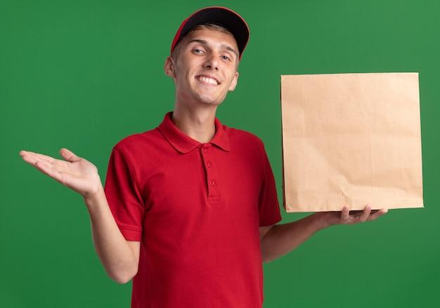 Lächelnder junger blonder lieferjunge hält hand offen und hält papierpaket isoliert auf grüner wand mit kopienraum
